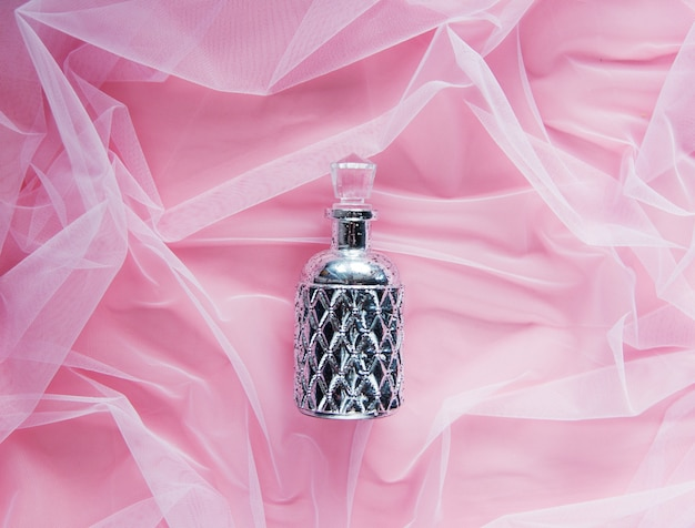 Butelka perfum na tle różowego tiulu. powyżej widok