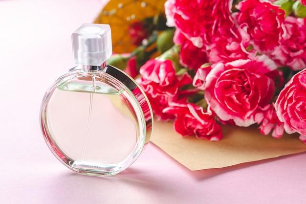 Butelka perfum osoby i bukiet kwiatów na różowej powierzchni. daj prezenty i kwiaty osobie. otrzymuj prezenty od bliskich na wakacje