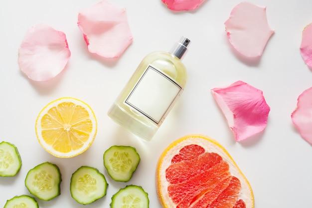 Butelka perfum ozdobiona płatkami róży, pokrojonym ogórkiem i cytryną z soczystym grejpfrutem, na białej ścianie, widok z góry. pojęcie składników lub kompozycji olejków perfum i olejków eterycznych