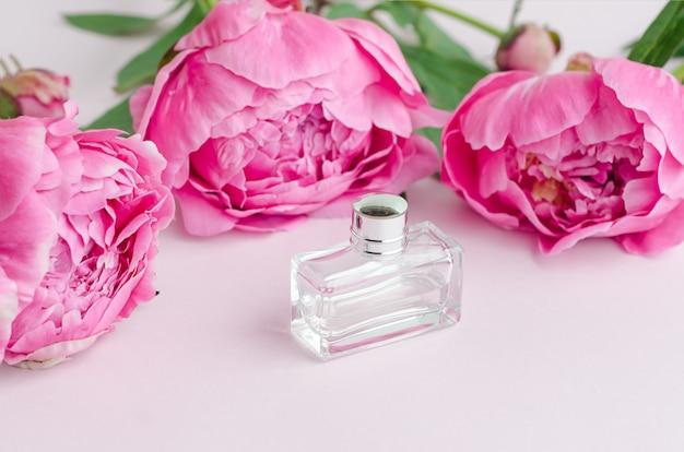 Butelka perfum, różowe piwonie. kwiatowy aromat piwonii