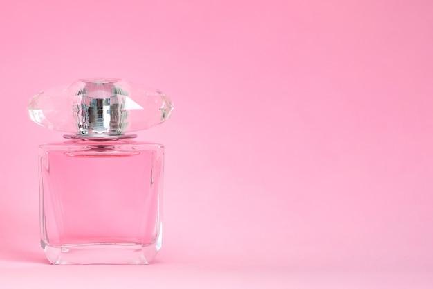 Butelka perfum spryskana na różowym pastelowym tle