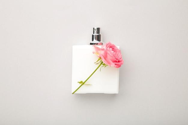 Butelka perfum z różową różą na szarym tle.