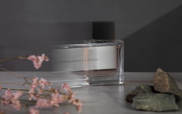 Butelka perfum z różowymi kwiatami na ciemnoszarym tle. biała etykieta na białym tle. skopiuj miejsce