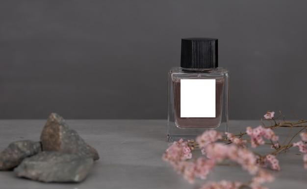 Butelka perfum z różowymi kwiatami na ciemnoszarym tle biała na białym tle etykieta biała na białym tle