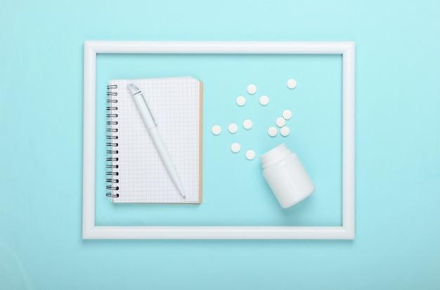 Butelka pigułki i notatnik na niebieskiej powierzchni z białą ramką
