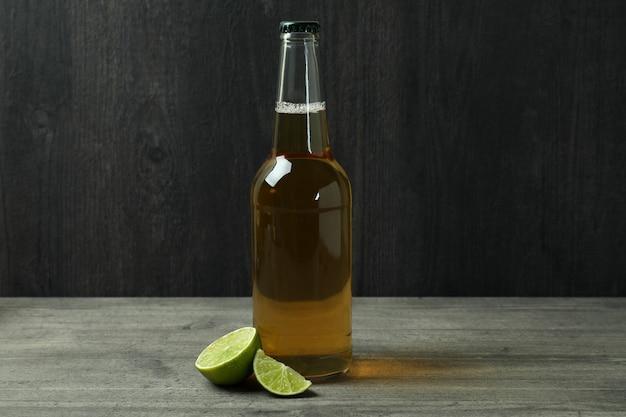 Butelka piwa i limonki na ciemnym drewnianym