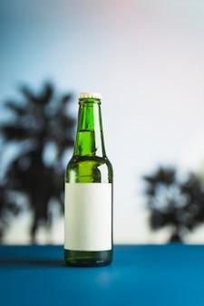 Butelka piwa na niebieskim stole