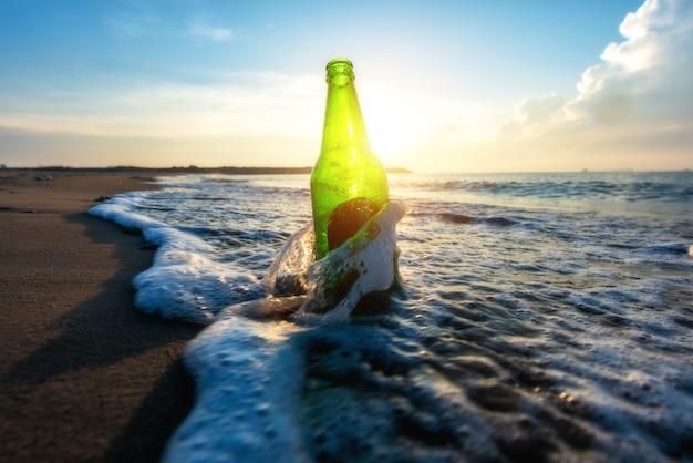 Butelka piwa na piaszczystej plaży z czystym niebem i falą