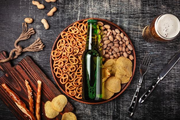 Butelka piwa na talerzu z solonymi precelkami ookies, pistacjami i frytkami na czarnej porysowanej tablicy kredowej