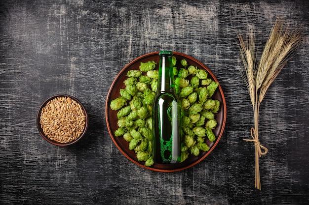 Butelka piwa na zielonym chmielu w talerzu z ziarna i spikelets pszenicy na tle