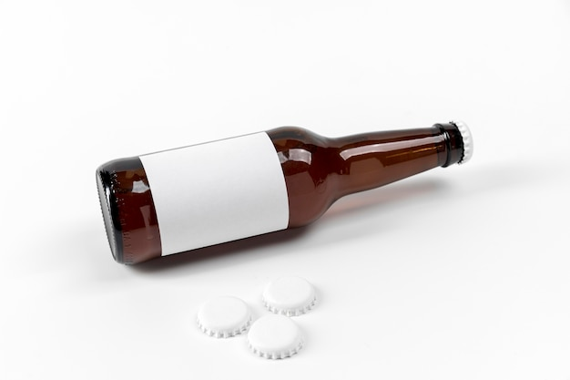 Butelka piwa pod wysokim kątem z pustą etykietą i nakrętkami