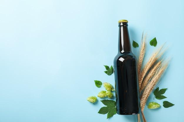 Butelka piwa, pszenicy i chmielu na niebiesko