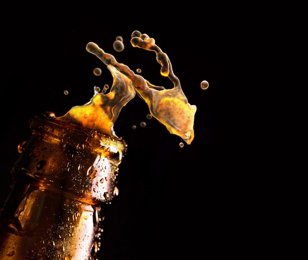 Butelka piwa z spadającą kroplą wody