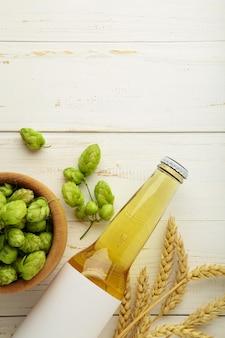 Butelka piwa z szyszek chmielowych i pszenicy na białym tle, z bliska. zdjęcie pionowe
