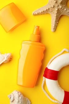 Butelka przeciwsłoneczna z akcesoriami plażowymi na żółtym tle.