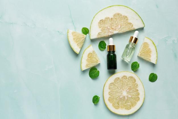 Butelka serum oleju grejpfrutowego umieścić na zielonym tle światła