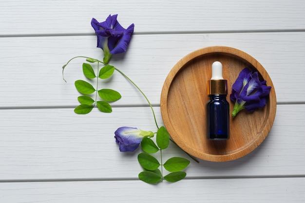 Butelka serum z olejkiem z kwiatu grochu motyla nałożona na drewnianą tackę
