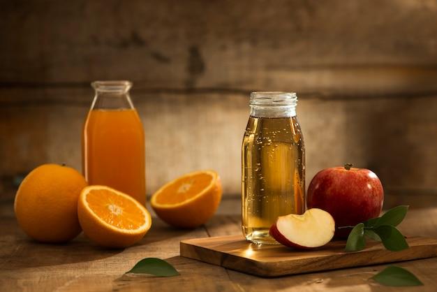 Butelka soku jabłkowego i pomarańczowego na białym tle na drewnianym tle