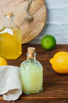 Butelka soku z cytryny z butelką soku z cytryny, biała szmatka na drewnianej i białej powierzchni, wysoki kąt widzenia.