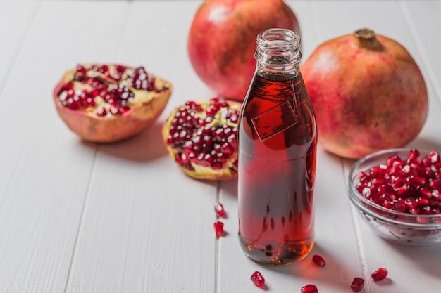 Butelka soku z granatów i dojrzałe granaty na białym stole. napój przydatny dla zdrowia.