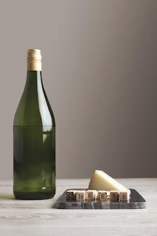 Butelka soku z zielonego wina winogronowego w pobliżu kamiennej marmurowej płyty z drewnianymi literami sera i koziego sera na białym tle na białym pustym tle i stole