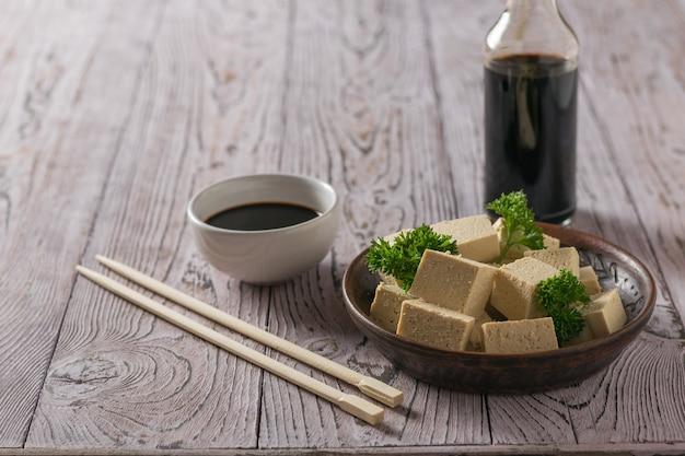 Butelka sosu sojowego i plasterki sera tofu na drewnianym stole. ser sojowy. produkt wegetariański.