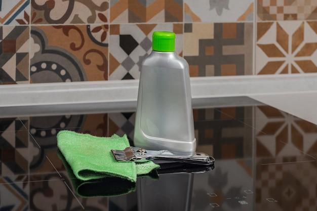 Butelka środka do czyszczenia płyty kuchennej skrobak do czyszczenia kuchenki i zielona ścierka sójka na kuchence
