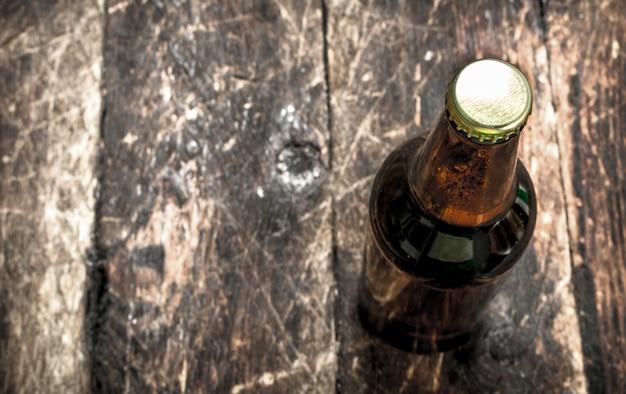 Butelka świeżego piwa na drewnianym stole.