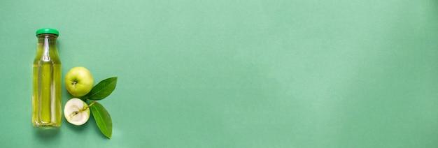 Butelka świeżego soku jabłkowego wzór płasko leżał widok z góry zielone tło z miejsca na kopię