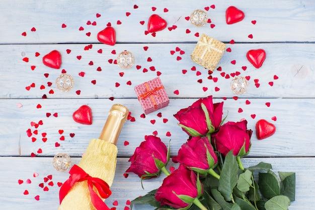 Butelka szampana, bukiet czerwonych róż i dwa prezenty w pudełku