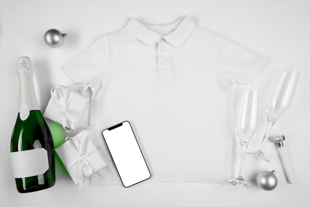 Butelka szampana i kieliszki obok telefonu komórkowego