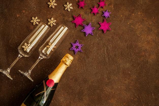 Butelka szampana i szklanki dla pary. fontanna gwiazd i płatków śniegu. świąteczny nastrój. szczęśliwego nowego roku