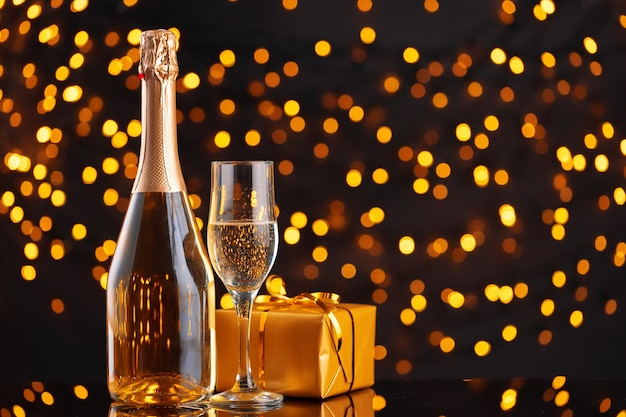 Butelka szampana i zapakowany prezent na niewyraźne świąteczne lampki