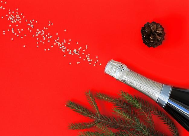 Butelka szampana na czerwonym papierze ze srebrnymi konfetti. boże narodzenie i nowy rok.