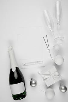 Butelka szampana obok karty i pióra