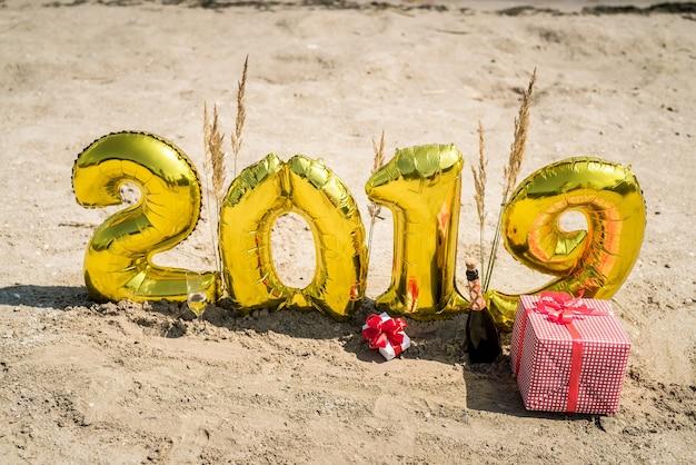 Butelka szampana, pudełka na prezenty i balony na plaży