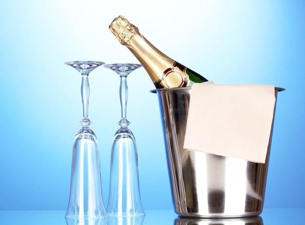 Butelka szampana w wiadrze z lodem i szklankami na niebieskim tle