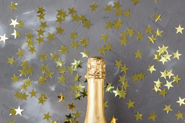 Butelka szampana w złote gwiazdki konfetti. koncepcja na boże narodzenie, nowy rok, urodziny lub ślub