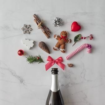 Butelka szampana z dekoracją świąteczną na marmurowej ścianie. leżał na płasko. koncepcja partii.