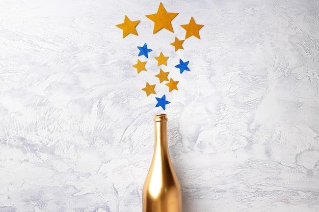 Butelka szampana z konfetti płasko leżała widok z góry