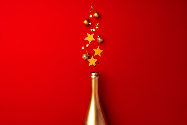 Butelka szampana z musującym konfetti na czerwonym płaskim ułożeniu