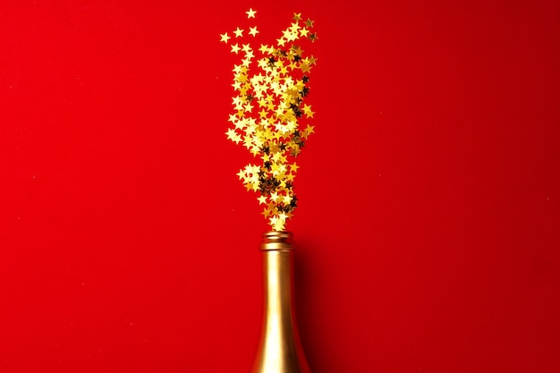 Butelka szampana z musującym konfetti na czerwonym płaskim widoku z góry