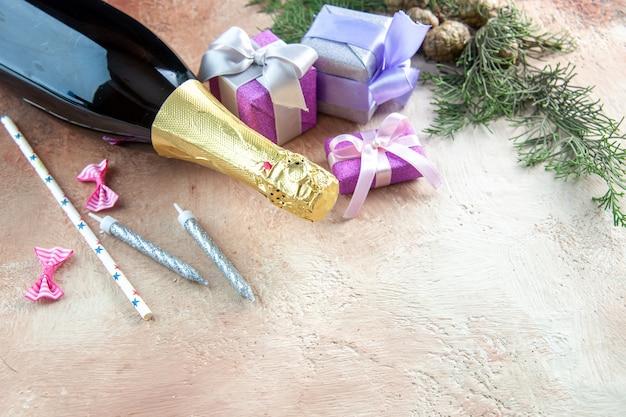 Butelka szampana z widokiem z przodu z małymi prezentami na jasnym tle