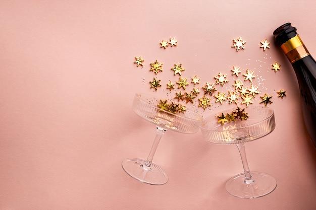Butelka szampana ze złotymi błyszczącymi plamami i kieliszkami do szampana na różowym tle płaskim lay