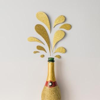Butelka szampana ze złotymi błyszczącymi plamami na białej powierzchni