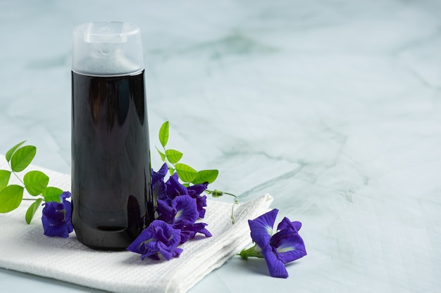 Butelka szamponu butterfly pea flower nałożona na białym marmurowym tle