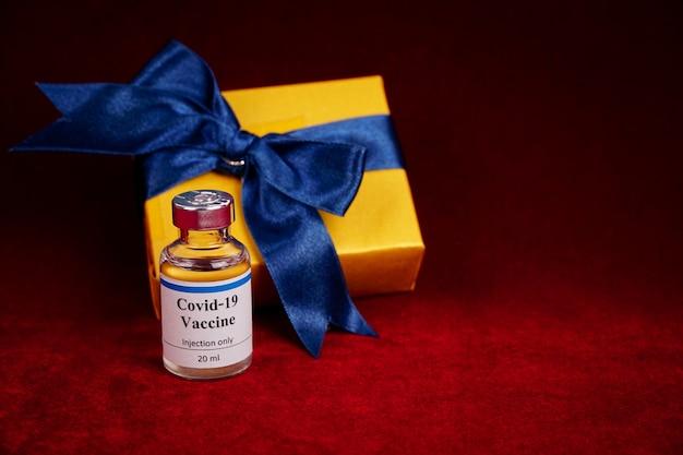 Butelka szczepionki na koronawirusa z pudełkiem prezentowym rozmytym na czerwonym tle