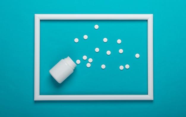 Butelka tabletek na niebieskiej powierzchni z białą ramką