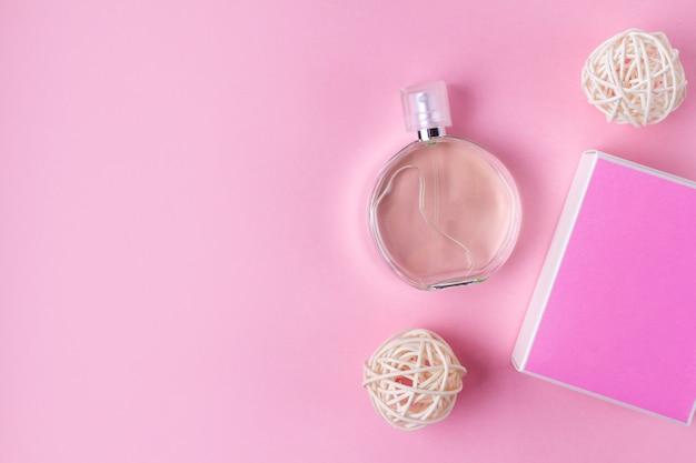 Butelka ulubionych damskich perfum na różowym tle.