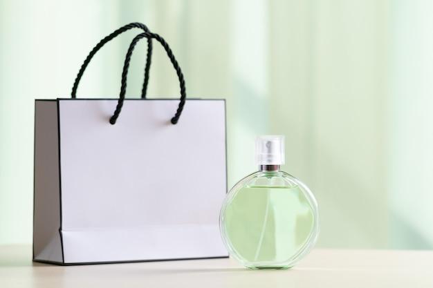 Butelka ulubionych kobiecych perfum i papierowa torebka na prezenty